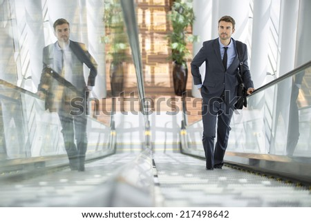 Businessman smiling with his own reflection at the escalator