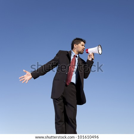 Businessman speaking with a megaphone with the blue sky as background (wide format photo)