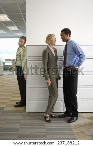 Businessman Spying on Coworkers - stock photo
