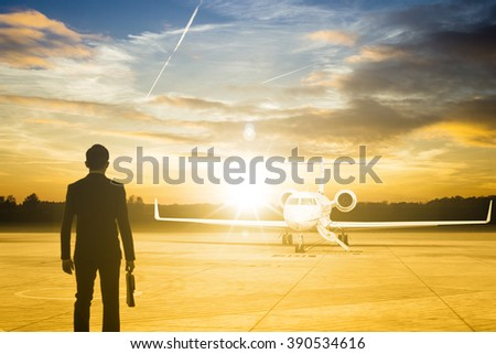 Businessman stand for go to passenger Jet airplane stop for wait VIP passenger on runway.  - stock photo