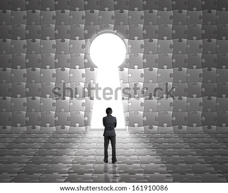 Businessman stand toward key hole shape door on puzzles wall with bright outside background - stock photo