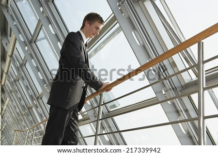 Businessman standing against a railing and looking down
