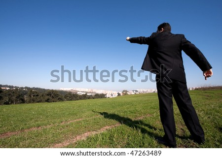 businessman standing alone at the field pointing away - stock photo