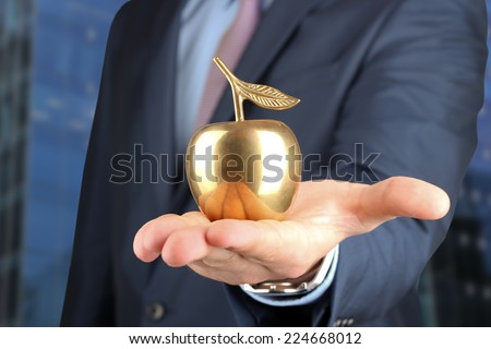 Businessman  standing  and holding golden  apple in his hand.  - stock photo