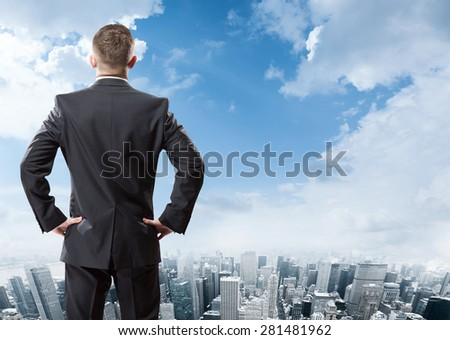 Businessman standing and looking at the city