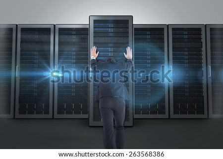 Businessman standing and pushing with hands against server towers