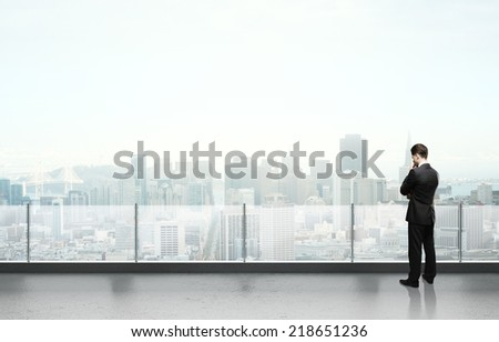 businessman standing and thinking on roof - stock photo