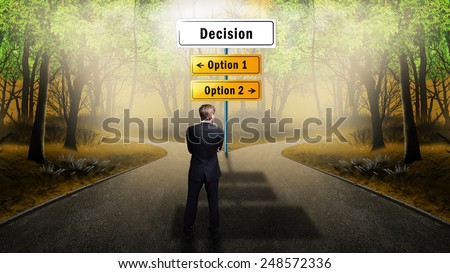 businessman standing at a crossroad having to 2 options where to go - stock photo