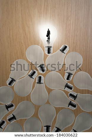 businessman standing at 3d growing light bulb standing out from the unlit incandescent bulbs as leadership concept - stock photo