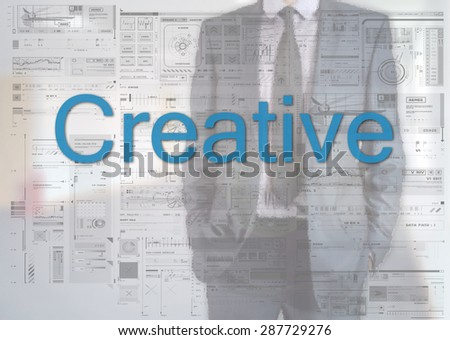Businessman standing behind transparent board with diagrams and text Creative