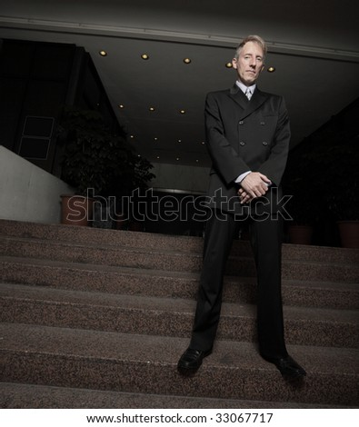 Businessman standing by a building entrance