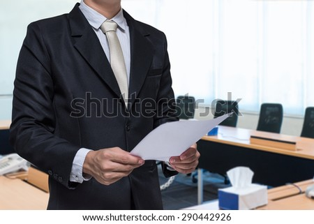 Businessman standing hand holding paper on meeting room background - stock photo