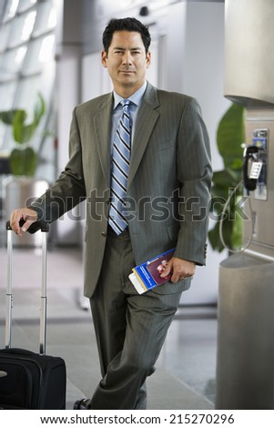 Businessman standing in airport terminal with luggage and ticket, smiling, portrait
