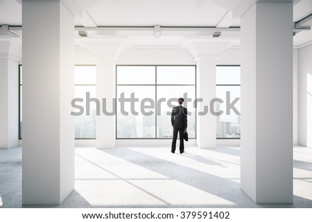 businessman standing in empty office interior with window - stock photo
