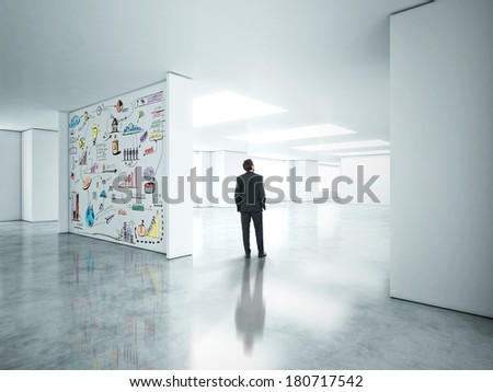 Businessman standing in empty office with strategy drowned on a wall - stock photo