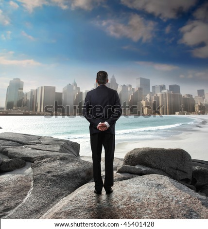 Businessman standing in front of a coastline and observing a cityscape on the background - stock photo