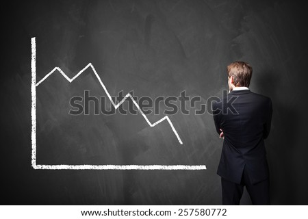 businessman standing in front of a decreasing chart on a blackboard - stock photo