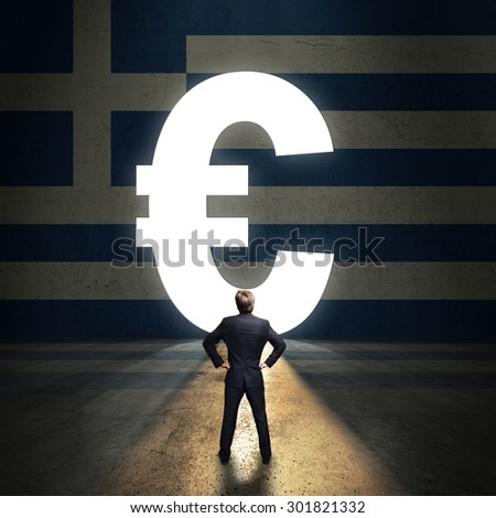 businessman standing in front of a portal shaped as Euro in a wall painted with the greek flag