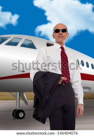 Businessman standing in front of a private plane  - stock photo