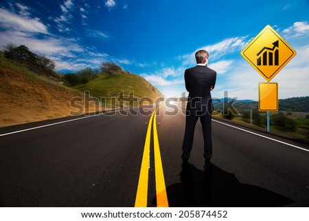 businessman standing in front of a sign with a chart on a windy road - stock photo