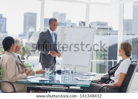 Businessman standing in front of a whiteboard during a meeting - stock photo