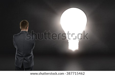 Businessman standing in front of bright big idea light bulb looking like a door - stock photo
