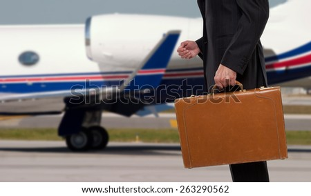 Businessman standing in front of corporate jet - stock photo