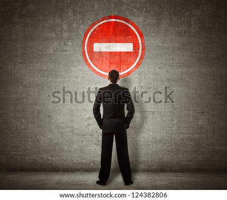 Businessman standing in front of no entry sign - stock photo