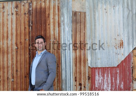 Businessman standing in front of sheet metal wall - stock photo