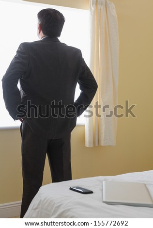 Businessman standing in front of window in a bedroom