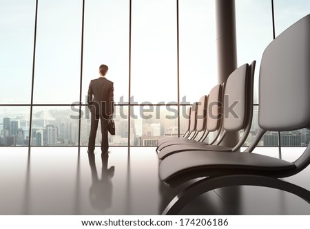 businessman standing in futuristic office with luggage