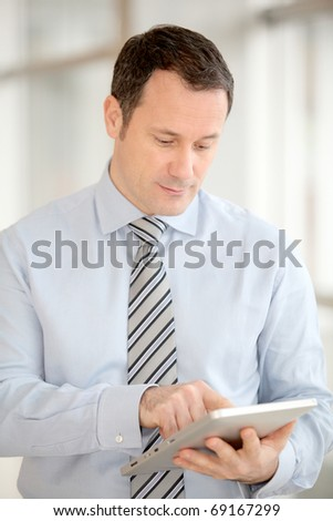 Businessman standing in hall with electronic tab - stock photo