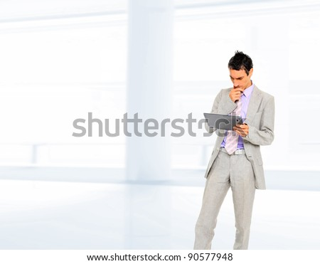 Businessman standing in hall with electronic tablet PC