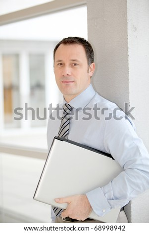 Businessman standing in hall with laptop computer - stock photo