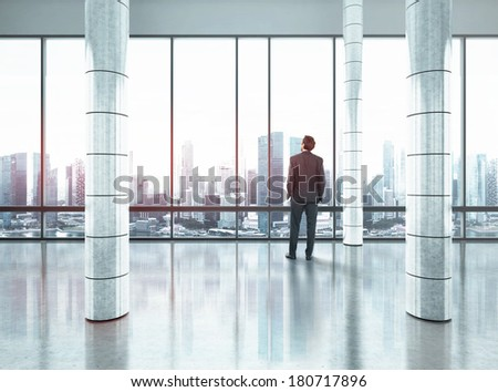 Businessman standing in large office and looking at city - stock photo