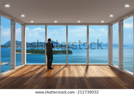 Businessman standing in modern lounge area with large bay window and view of sea - stock photo