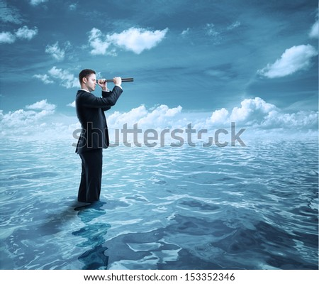businessman standing in ocean and  looking through a telescope - stock photo