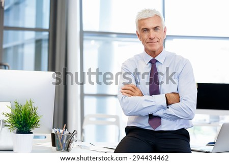 Businessman standing in office smiling at camera - stock photo