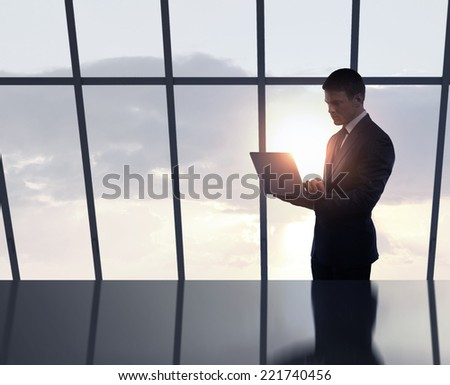 businessman standing in office with laptop in hand - stock photo