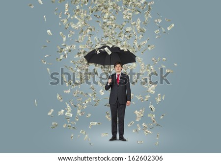 Businessman standing in the rain of dollars over grey background