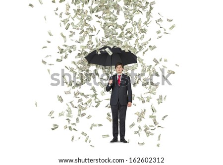 Businessman standing in the rain of dollars over white background - stock photo