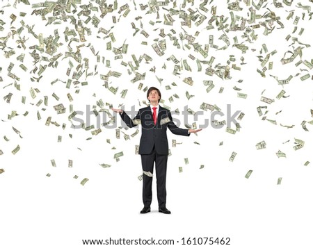 Businessman standing in the rain of money. 1,5,10,20,50,100 dollar bills