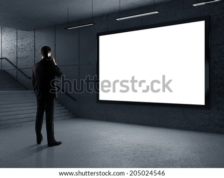 businessman standing in underground passage with phone - stock photo