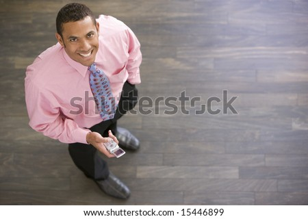 Businessman standing indoors with cellular phone smiling - stock photo