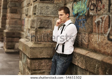 businessman standing near old stone wall - stock photo