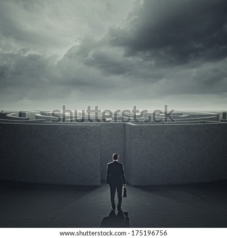 Businessman standing near the enter of labyrinth