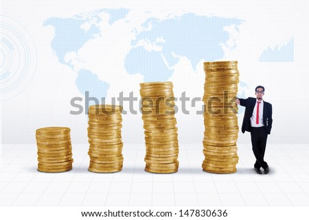 Businessman standing next to gold coins chart on world map background