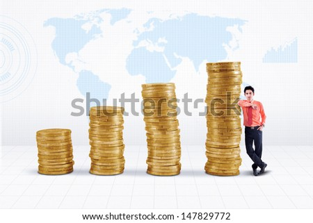 Businessman standing next to gold coins growth chart on world map