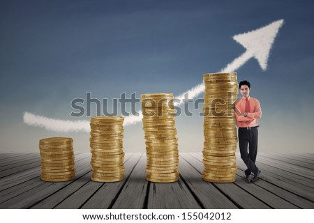 Businessman standing next to gold coins growth chart with arrow sign