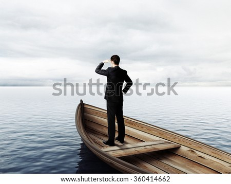 businessman standing on a boat and looking on ocean - stock photo